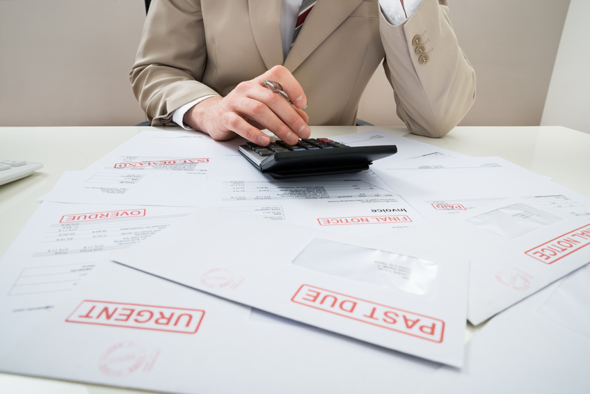Close-up Of Businessman Calculating With Calculator Unpaid Bills